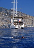 Small cruise ship Le Ponant passengers swimming off coast of Corsica in the Mediterranean Sea.