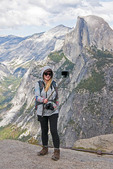 Yosemite National Park with photographer doing a selfie at Glacier Point overlook with Half Dome in background.