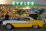 Art deco Avalon Hotel with classic Oldsmobile on Ocean Drive in South Miami Beach in evening.