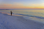 Boy fishing at sunset on Siesta Key Beach at Sarasota, Florida.