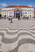 Wavy pavement of Portuguese tiles in Lisbon's Rossio Square with Dona Maria II National Theater and Baroque fountain.