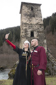 Georgian couple in traditional dress taking a selfie at the Tower of Love in Upper Svaneti region of Caucasus Mountains.