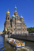 Tourists in canal tour boat passing Our Savior Church on Spilled Blood in St. Petersburg, Russia.