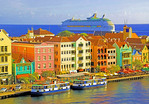 Willemstad, Curacao: Punda waterfront pastel Dutch architecture with Royal Caribbean cruise ship Adventure of the Seas leaving port