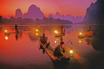 Cormorant fishermen lighting lanterns for night fishing on Li River at Xingping (Guilin area)