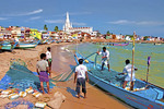 Fishermen on Kanyakumari Beach waterfront preparing nets with Our Lady of Ransom Church in background.