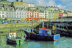 View from the Cobh harbour of fishing boats and store fronts in County Cork, Ireland