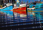 Reflections of fishing boats in Hout Bay Harbour, Western Cape, South Africa