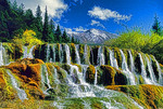 Songpan County, Sichuan, China: Liantai Waterfalls in Huanglong Scenic Area with Huanglong (Yellow Dragon) Peak above.