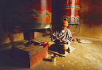 Thimphu, Bhutan, pilgrim with prayer wheels in memorial chorten of King Wangchuck.