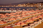 Pink umbrellas and beach chairs along the French Riviera at Cannes, France.