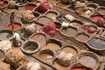 Workers in vats dyeing animal hide to be made into slippers (babouche) at famous tanneries of Fes, Morocco.