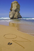 Beach with flip flops and OZ sign at 12 Apostles on the Great Ocean Road, Victoria, Australia.
