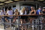 Summer weekend drinkers on Manly Wharf Hotel porch, NSW, Australia.