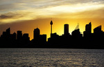 Sunset silhouetting Sydney skyline.