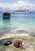 Sea Princess passenger on beach at Doini Island with cruise ship in background.