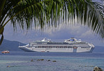 Passengers from the cruise ship Sea Princess snorkeling in the foreground of the ship in Milne Bay at Doini Island in Papua New Guinea.