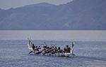 Melanesian warriors on Milne Bay in dugout war canoe, Alotau, Papua New Guinea.