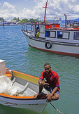 Young man on boat at Alotau Harbour on Milne Bay, Papua New Guinea.