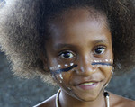 Melanesian girl in tribal festival dress dancing at Alotau, Papua New Guinea.