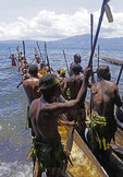 Melanesian islanders with dugout war canoes at Alotau, Papua New Guinea.