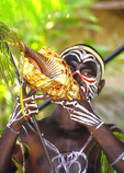 Melanesian tribal warrior in cultural festival dress blowing on shell horn at Alotau, Papua New Guinea.