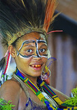 Young Melanesian tribal woman with betel stains on her teeth in tribal festival dress at Alotau, Papua New Guinea.