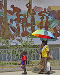 Woman and child passing historical culture mural in downtown Port Vila, Vanuatu.