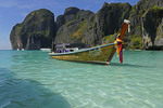 Thai long-tail boat decorated with sashes at Maya Bay of Phi Phi Leh island, Thailand.