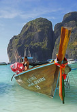 Woman shaking towel on Thai long-tail boat decorated with sashes at Ton Sai Bay of Phi Phi Leh island, Thailand.