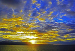 Golden sunrise from cruise ship over island in Coral Sea of South Pacific ocean.