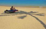 Sunbather in shade of palm tree at Bophut Beach, Koh Samui, Thailand.