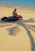 Sunbather in shade of palm tree at Bophut Beach, Koh Samui, Thailand.