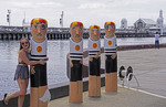 Waterfront wooden bollards of Geelong Baths Swimming Team with admirer and Cunningham Pier in background, Geelong, Victoria, Australia.