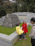 Mother with her two children visiting the tomb of Admiral Zheng He at his gravesite in Niushou Mountain Cultural Park near Nanjing.