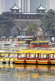 Boats for rental at Xuanwu Lake Park with Xuanwu Gate of old Nanjing city wall in background.