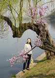 Young woman admiring plum blossoms in spring along Xuanwu Lake in Nanjing.