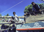 Boys watching Dhow being launched on waterfront of Swahili island of Lamu by community volunteers