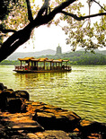 Hangzhou's West Lake with tourist boat along shore of Island of Small Seas with pagoda in distance.