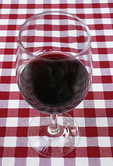 Red wine in glass on checkered table cloth at winery in Godinje Historical Village.  Photo painting - watercolor.
