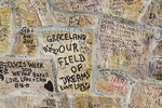 Grafitti from fans of Elvis Presley on stone wall in front of Graceland mansion.