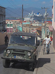 Jeep in port of Santiago de Cuba with cruise ship Adonia in harbor.