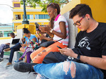 Young Cubans in Santiago de Cuba's Marti Plaza concentrating on using smart phones.