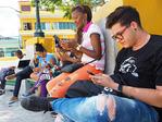 Young Cubans in Santiago de Cuba's Marti Plaza concentrating on using smart phones.