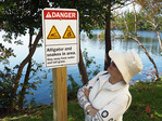 Miami, Florida, woman reading sign warning of danger of alligators and snakes next to lagoon.