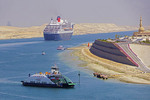 Suez Canal at Ismailia Crossing with Suez Ferry, north bound Queen Mary 2 cruise ship, and mosque.