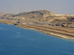 Sand excavated from new section of Suez Canal piled along north bound lane.