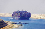 Container freighter and ferry at dock in Suez Canal.