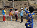 Chinese womwn tourists doing diagonal group photo (sic) at ruins of Olympia.