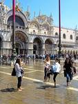 Tourists wading in flooded St. Mark's Square in Venice.